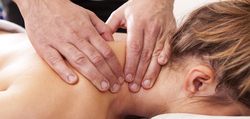 A massage therapist uses Swedish style massage to work the trapezius muscle on a patient.